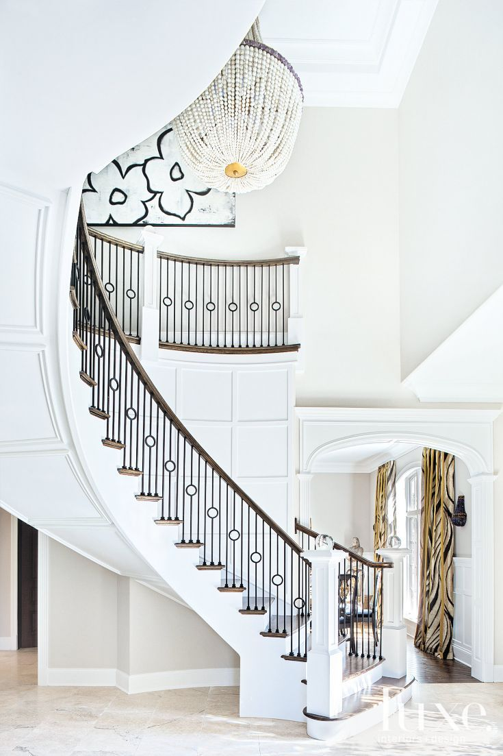 Interior designer Julia Buckingham Edelmann designed the grand staircase. Sleek new balusters, handrails and newel posts of Edelmann's own design diminish the foyer's baroque aesthetic and give it a more modern vibe. Here and elsewhere in the house, Edelmann used Benjamin Moore's icy Chantilly Lace.