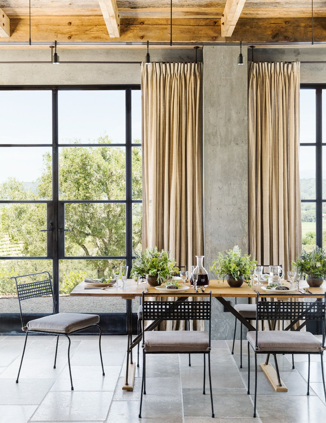 Tan curtains, wood dining table, grey tile flooring, and black chairs with grey seat cushions