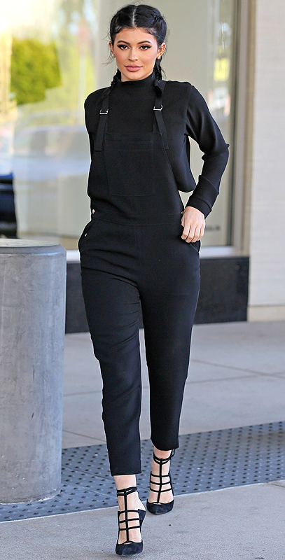 Kylie Jenner in black overalls, a turtleneck and pigtails