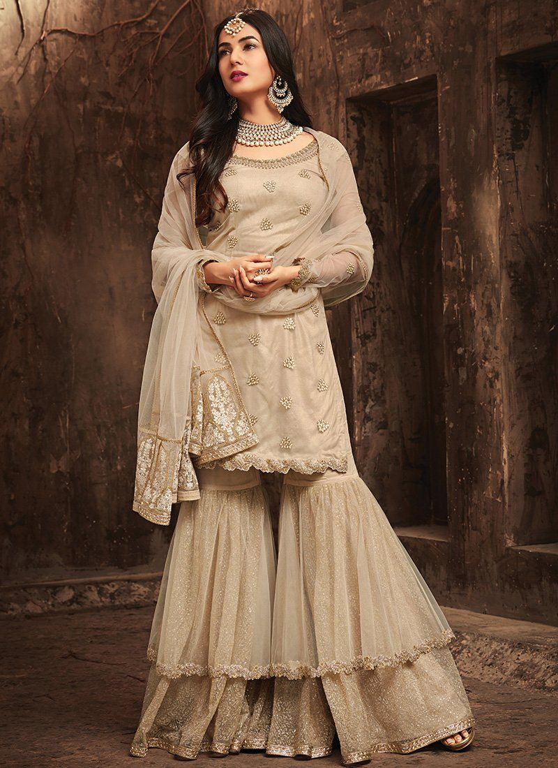A stunning Beige Sonal Chouhan Sharara Style Maisha Suit. Net top with Santoon Inner and Santoon and Net bottom, Net Dupatta. 100% Original Company Product with the HIGH-QUALITY fabric material. Free Delivery in India. #shararadesigns