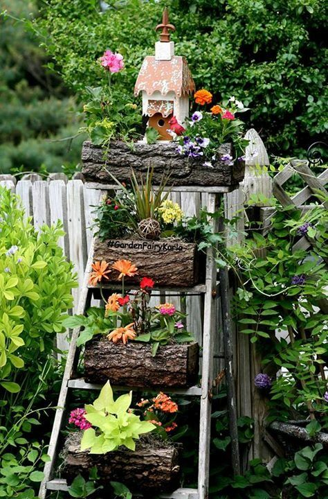 Every year, over 20 years, I redecorate one of my old ladders w/my log planters, and every year I love the look more and more! This creative, eye-catching and very unique display creates a wonderful conversation piece as well as being a great statement piece! #GardenFairyKarla #Gardening #PlantStand #OldLadder #Ladder #Repurpose #CreativeGardenIdeas #CottageGarden #BetterHomesAndGardens #Vintage #LogPlanters #UniquePlanters #Birdhouse #GardenDecor #NewInGardening #Trending #VintageLadder