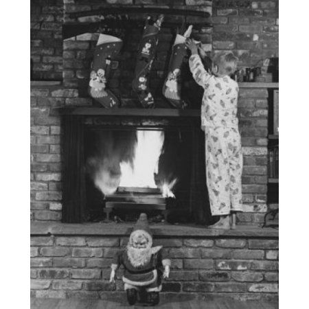 Rear view of boy standing on fireplace and grabbing Christmas stocking Canvas Art - (24 x 36)