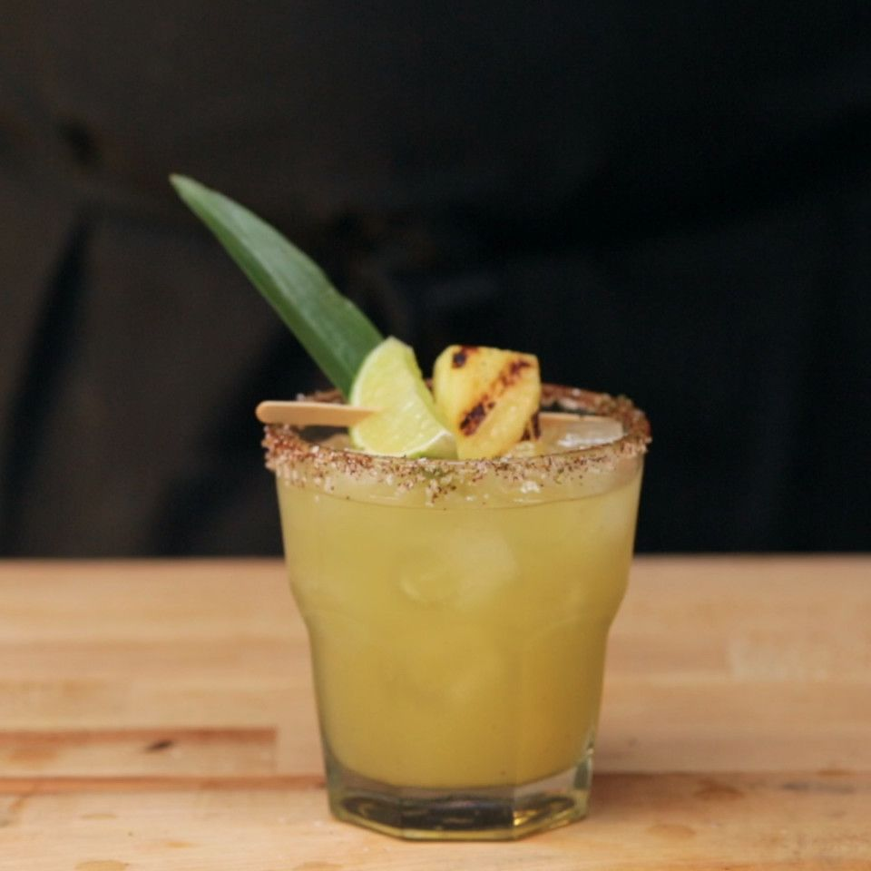 Recipe with video instructions: How to make grilled pineapple margaritas.  Ingredients: 1 pineapple, 3 cups pineapple juice, 8 oz silver tequila, 4 oz simple syrup, plus 2 tbsp reserved, 4 oz lime juice, 1 Tbsp sea salt, 1 Tbsp chili powder, 1 lime, zested