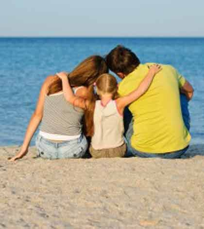 Father, mother, and a child sitting together and watching the ocean