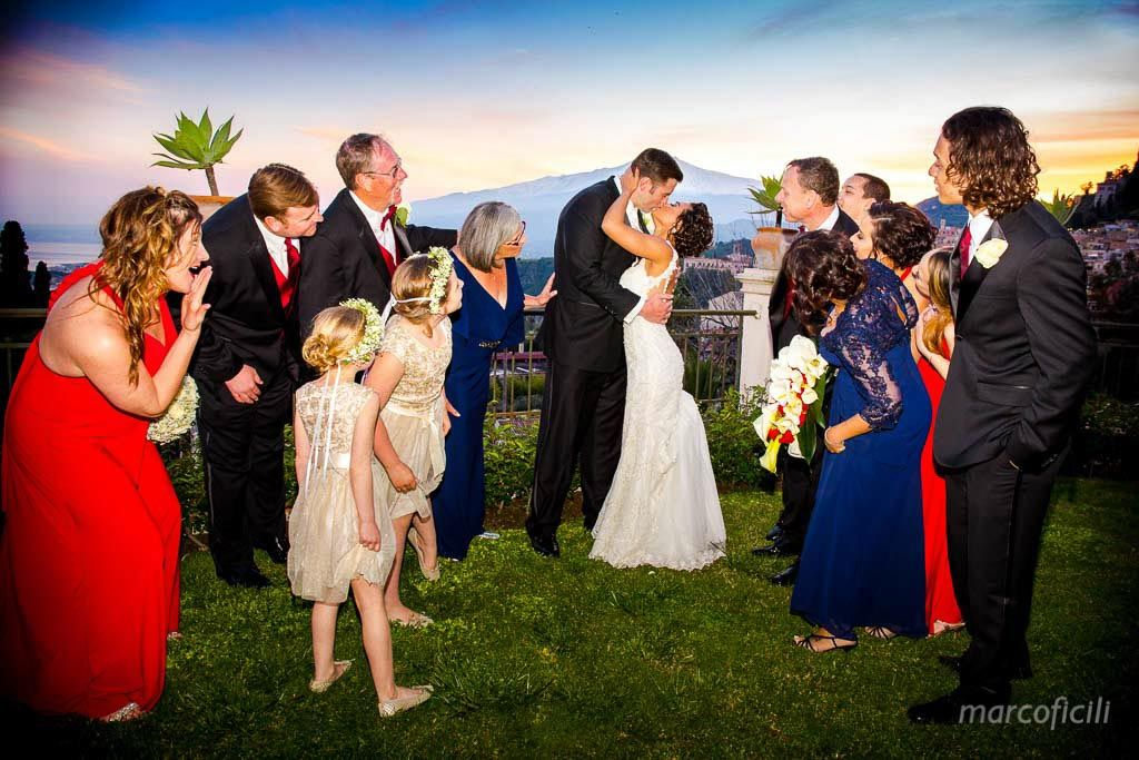 Amazing Bride & Groom kiss encircled by their families, during the sunset an the mount Etna in background.
