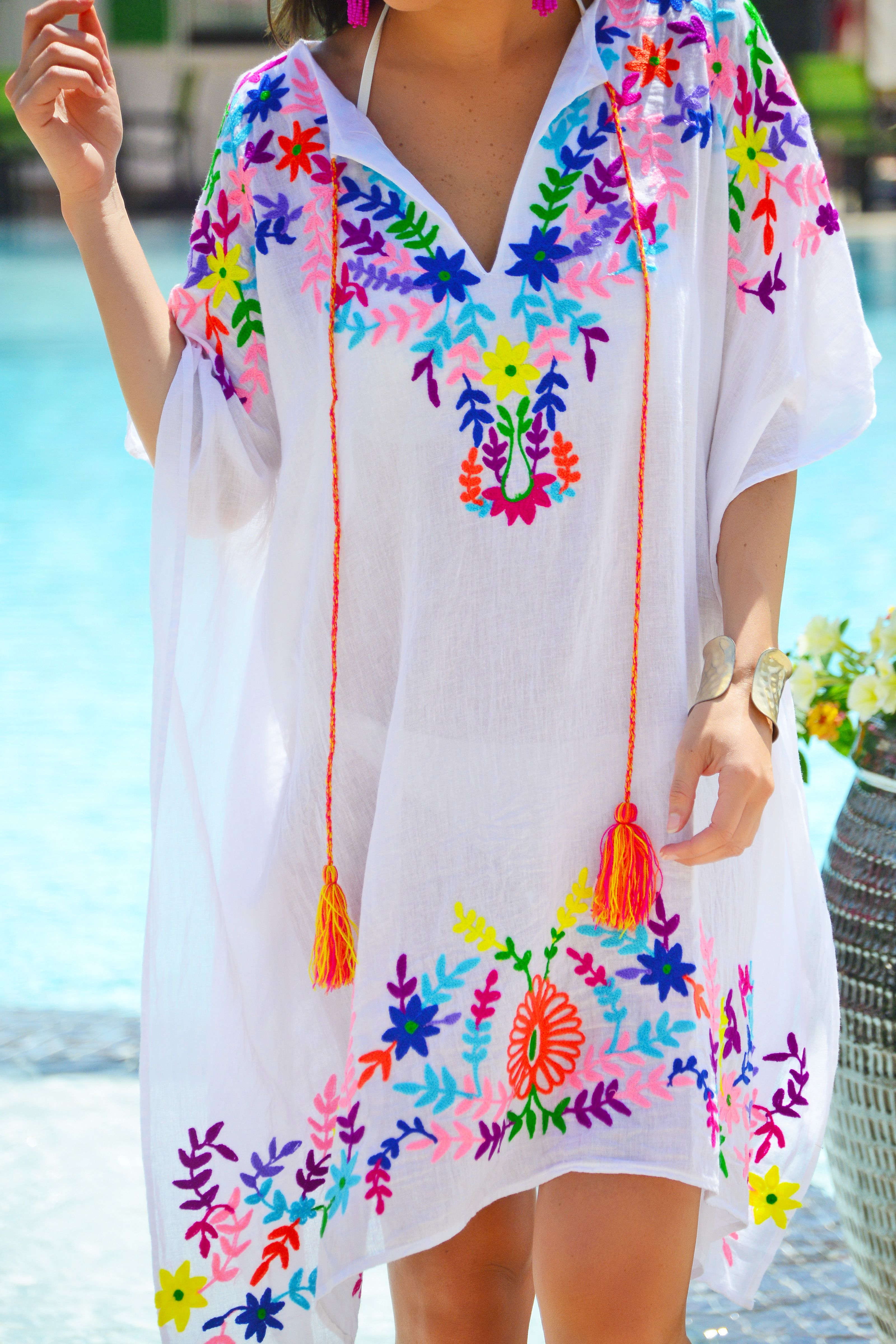 You'll be the envy of all around when you step out in this cute as can be kaftan! It boasts the prettiest, bright embroidery and is topped off by colorful tassel ties. Rock it over your swimsuit or over a slip. Fabric is a lightweight 100% cotton.
