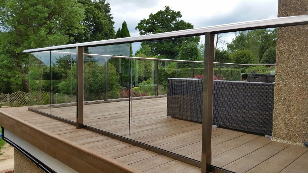 Glass balustrade composite decking surrey case study for Garden decking banister