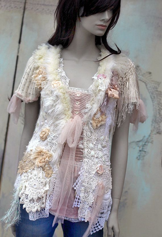 Whimsy angora blend cardi, altered couture, richly embellished with intricate details. The hems are adorned with vintage and antique laces, cream silk blooms, vintage french leaf-shaped sequins; the bold collarline is adorned with laces and tulle -stitched, textured, and adorned with handmade silk flowers, satin roses, and ivory art.fur trim. The jacket fastens with soft tulle ribbons. Will look great with jeans and simple white tshirt. Fits sz S measurements: (fastened at front ) bust 90…