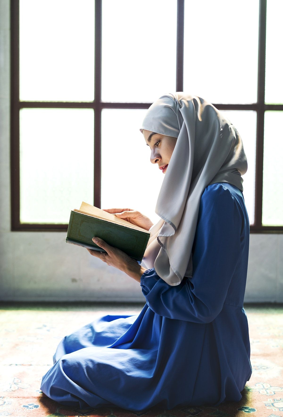 Download premium photo of Muslim woman reading from the