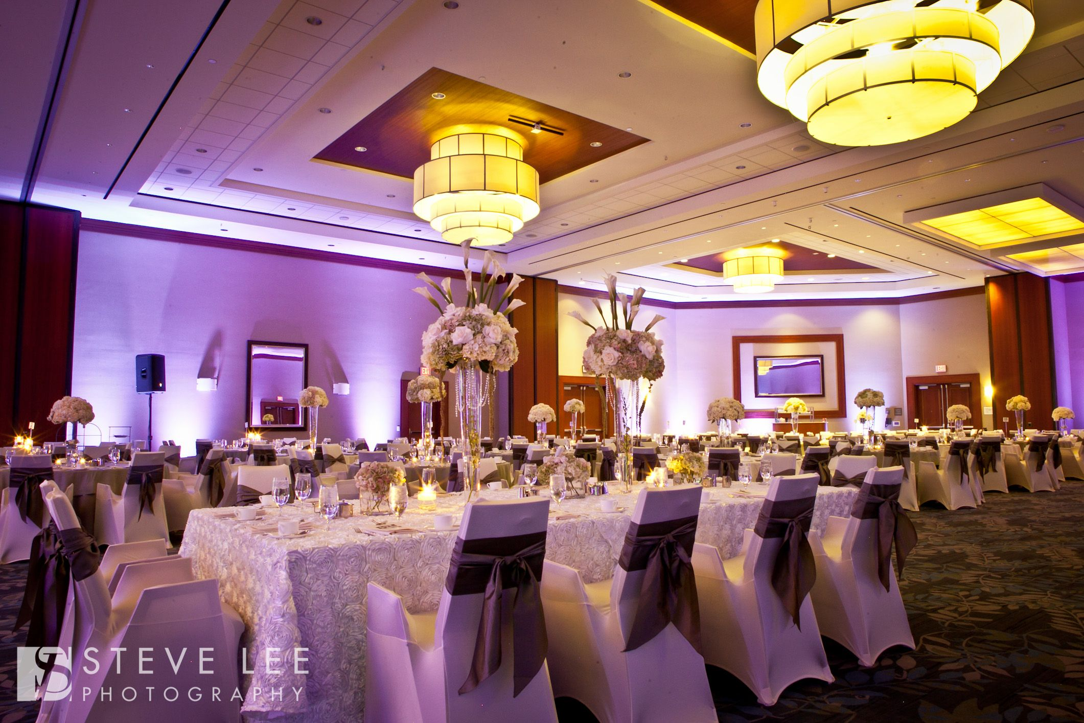 White spandex chair covers and a simple sash tie create a clean look for this ballroom event at The Westin Memorial City in Houston, Texas