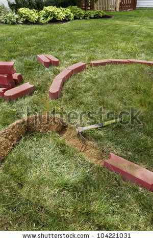 Laying brick edgers around the house for easy trimming and cutting the grass. - stock photo