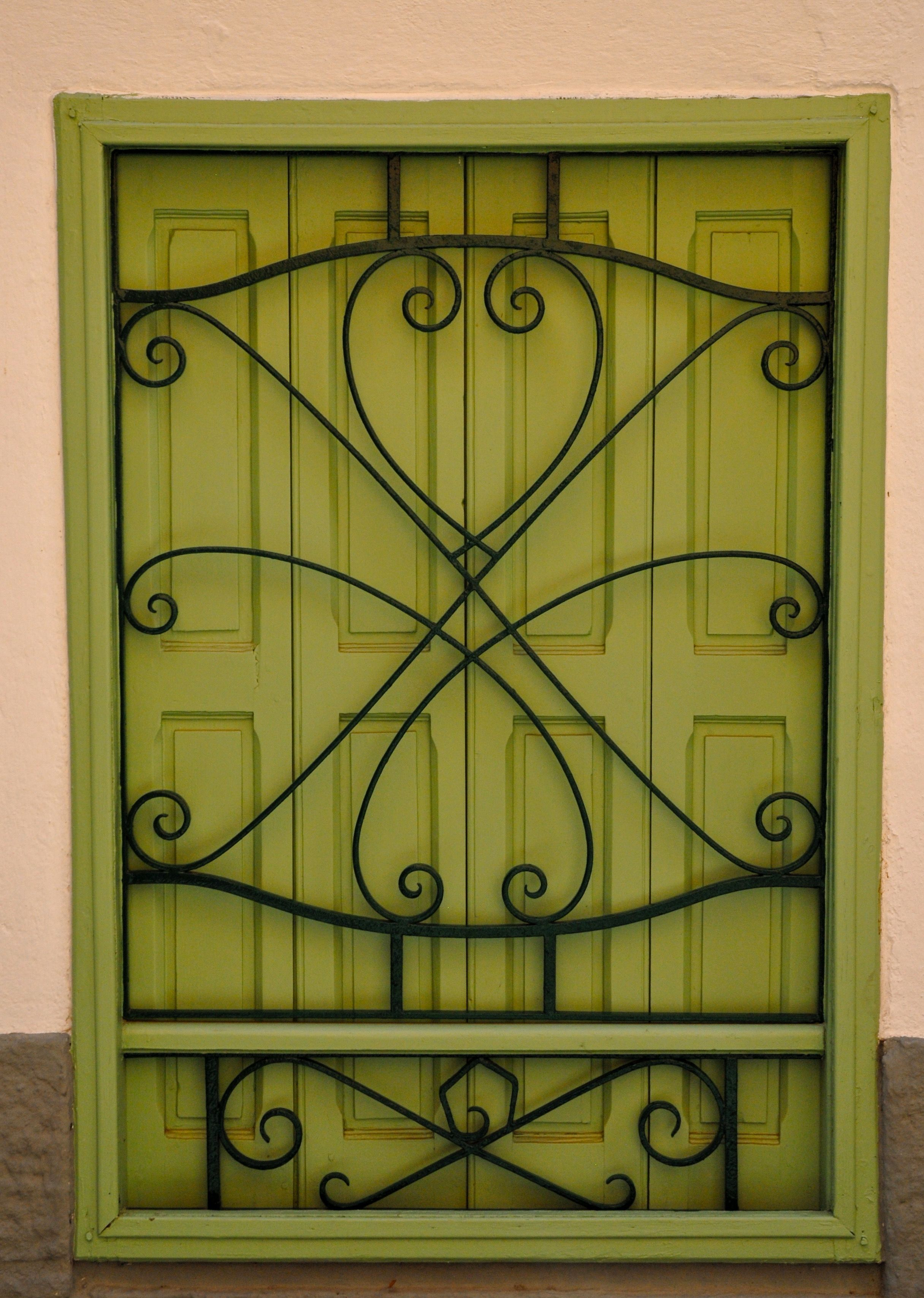 French Window With Closed Painted Shutters And Fancy Metalwork