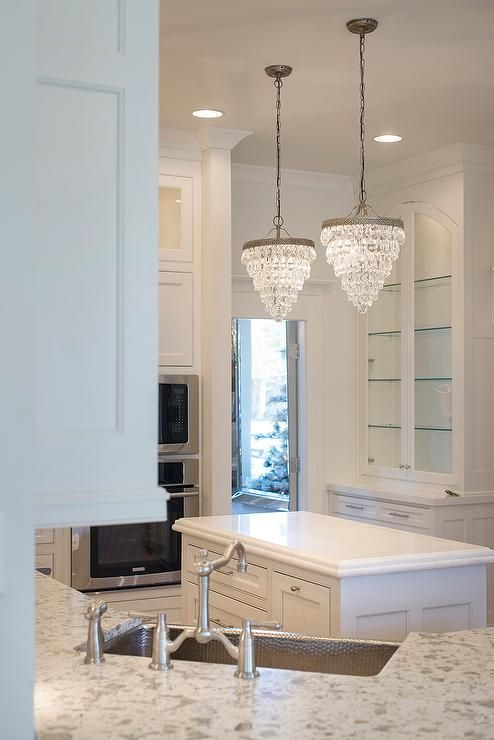 Two Pottery Barn Clarissa Crystal Drop Small Round Chandeliers Hang Over A  Small Kitchen Island Next To A Microwave Stacked Atop A Wall Oven.