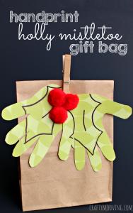 List of Christmas Crafts for Kids to Create #mistletoesfootprintcraft kids-handprint-holly-mistletoe-christmas-gift-bag-craft #mistletoesfootprintcraft