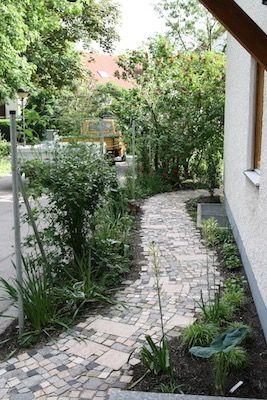 Geschwungener Weg aus buntem Pflaster. Zaun aus Metallpfosten mit Edelstahlseilen, die mit Kletterpflanzen berankt wurden. Schattenpflanzung.