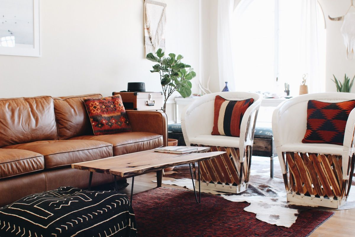 Love that graphic poof with the rich red persian rug and brown leather sofa also  cup of jo los angeles home tour living room inspiration