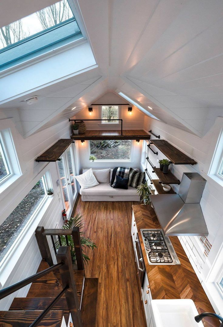 Das Wohnzimmer hat ein Panoramafenster über der Couch. Eine schwarze Pfeifenleiter führt ... #tinyhomes