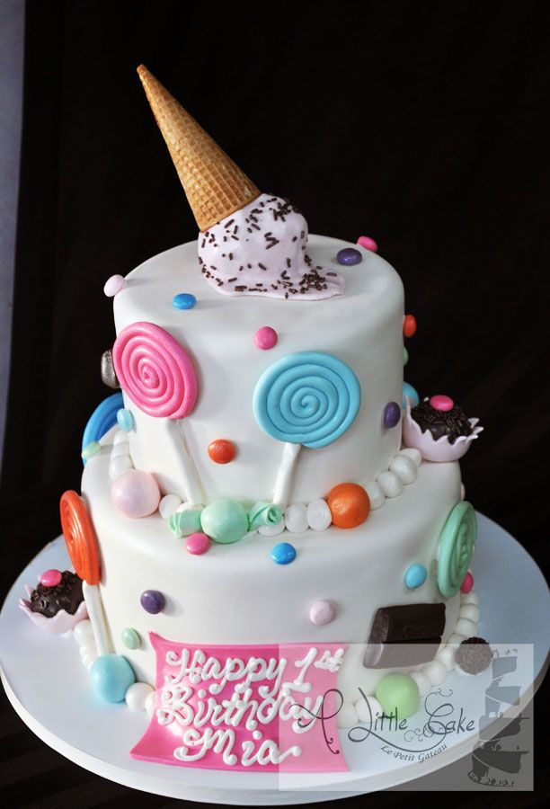 This 2 tier candy theme fondant iced cake was made for a first birthday