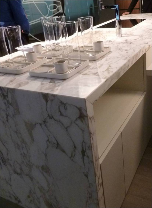 Designers are extending the countertop patterns down the sides to create stunning kitchen focal points. #waterfallcountertop