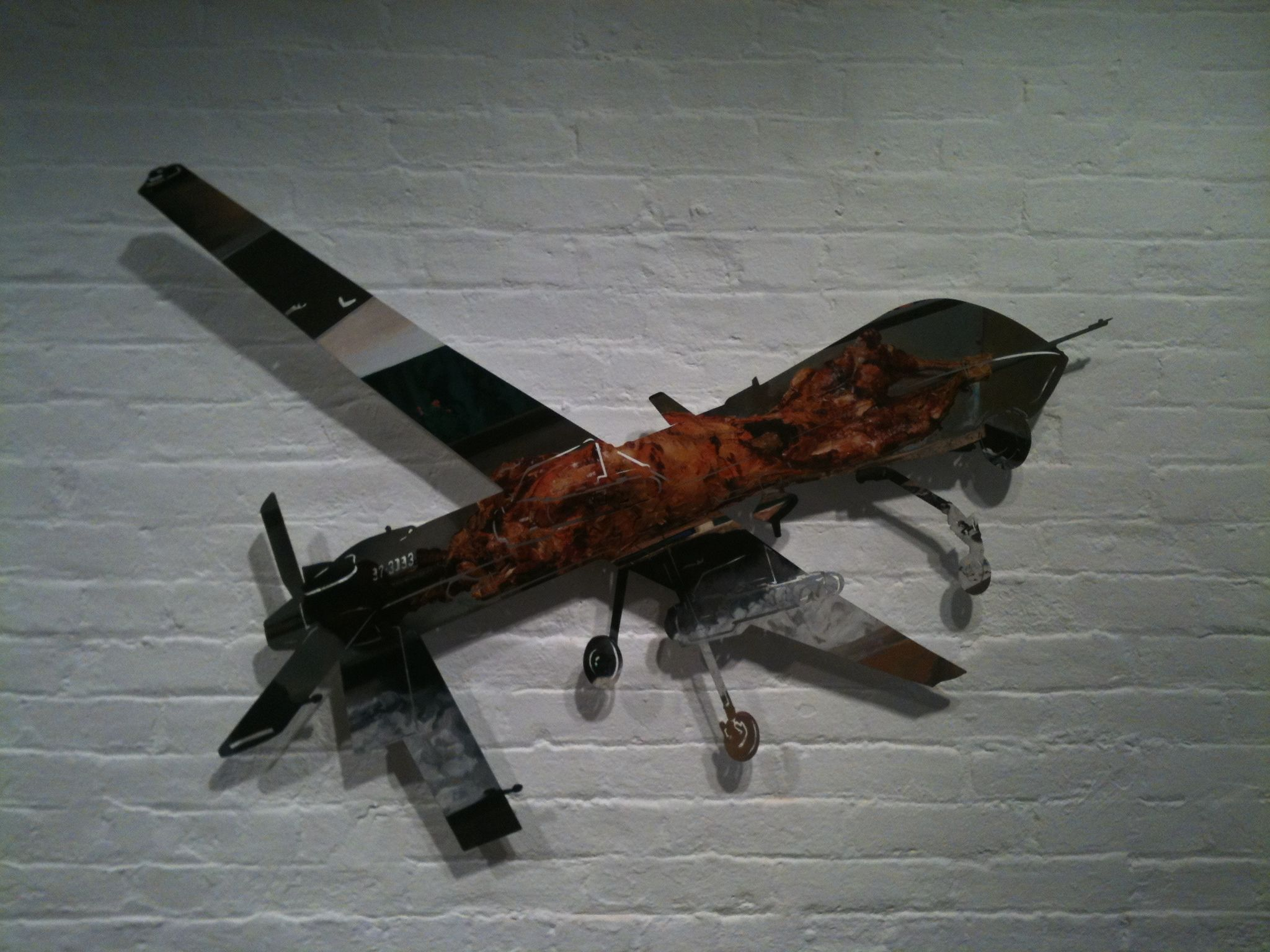 "Saw this piece in a gallery in Chelsea; a photo of a roasting goat cut in the shape of a predator drone.  In late 2012 some shepherds in Bahrain found a village destroyed by a drone attack.  According to the AP, they had to bury everything because they couldn't tell the goat meat from the human meat. The word for goat in Greek is ""tragos"", from which we get the word ""tragedy"".  Solid piece."