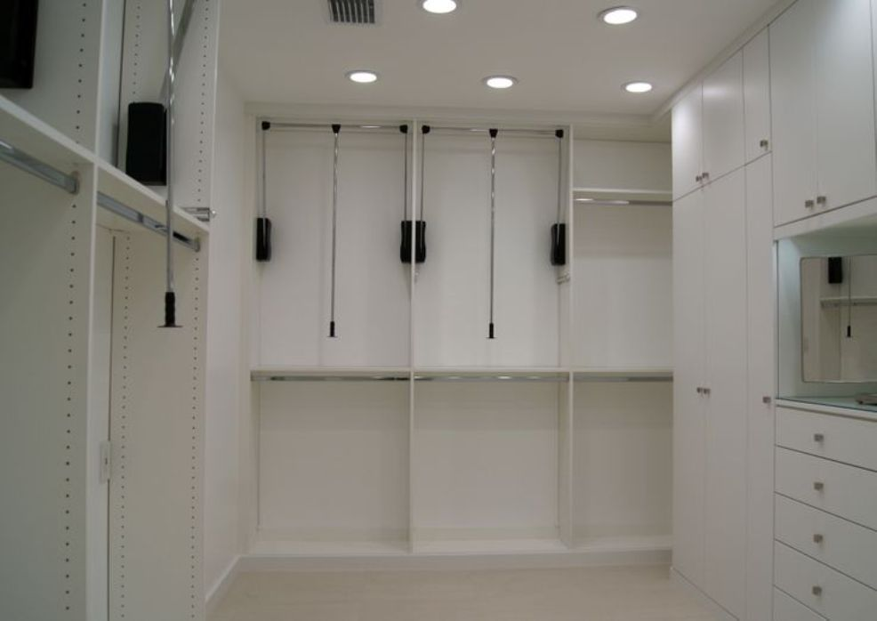 Pull Down Hanging Rods Utilize The High Ceilings In This Closet Space.  These Easy To Use Rods Eliminate The Need For A Step Stool.