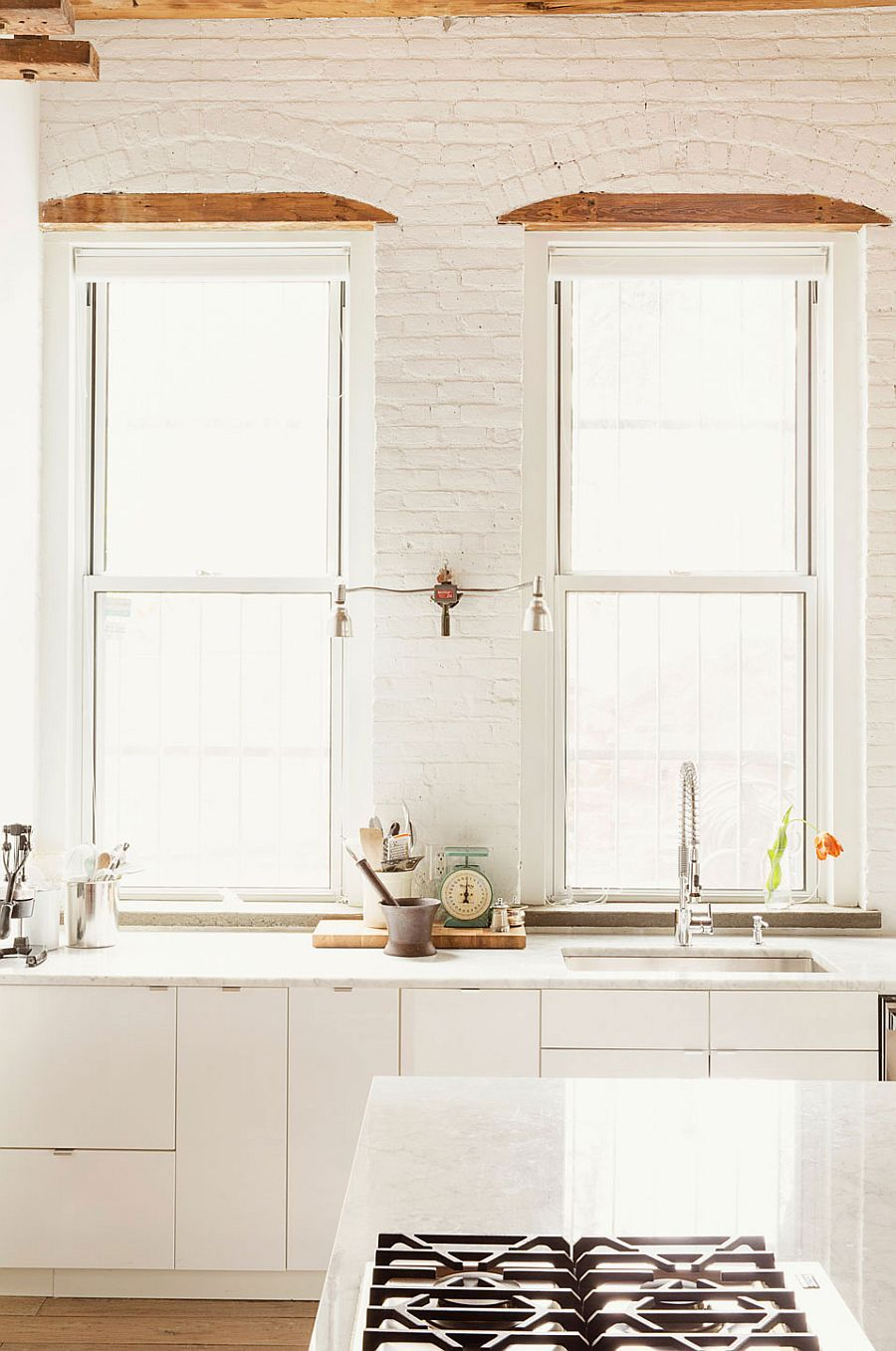 Window on wall decor  kitchen in white with exposed brick walls and large windows
