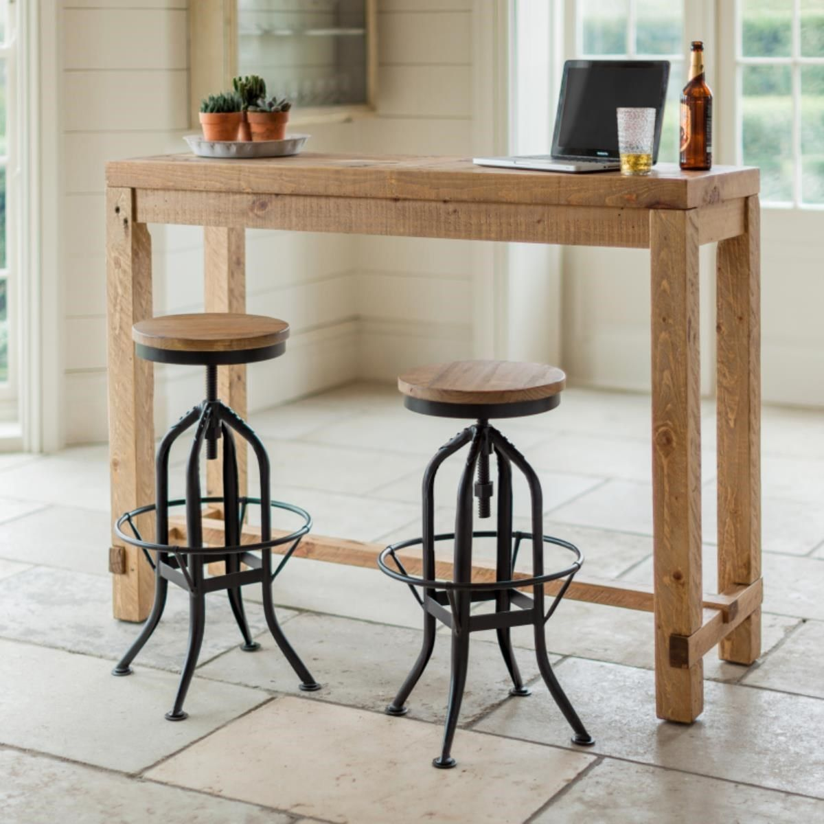 A tall bar table handcrafted from reclaimed pine in a ...