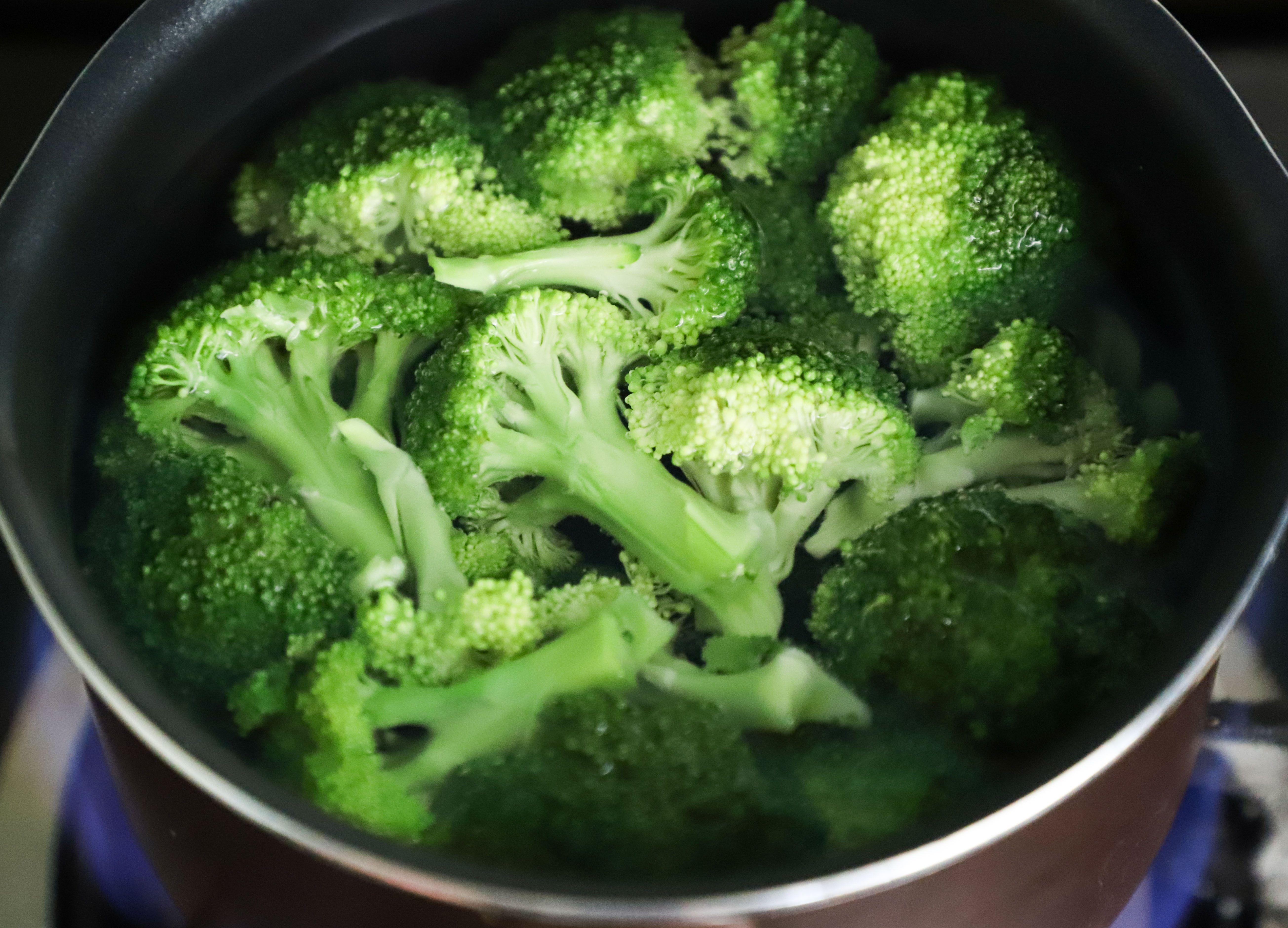 cacerola con brócoli en agua puesta al fuego