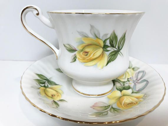 Happiness abounds with the bows and daisies surrounding the yellow roses. Royal Standard Bone China of England produced this shapely, charming tea cup and saucer. This is a company that is an acknowledged leader in fine design. It was owned by the Chapmans Longton Ltd from the Albert