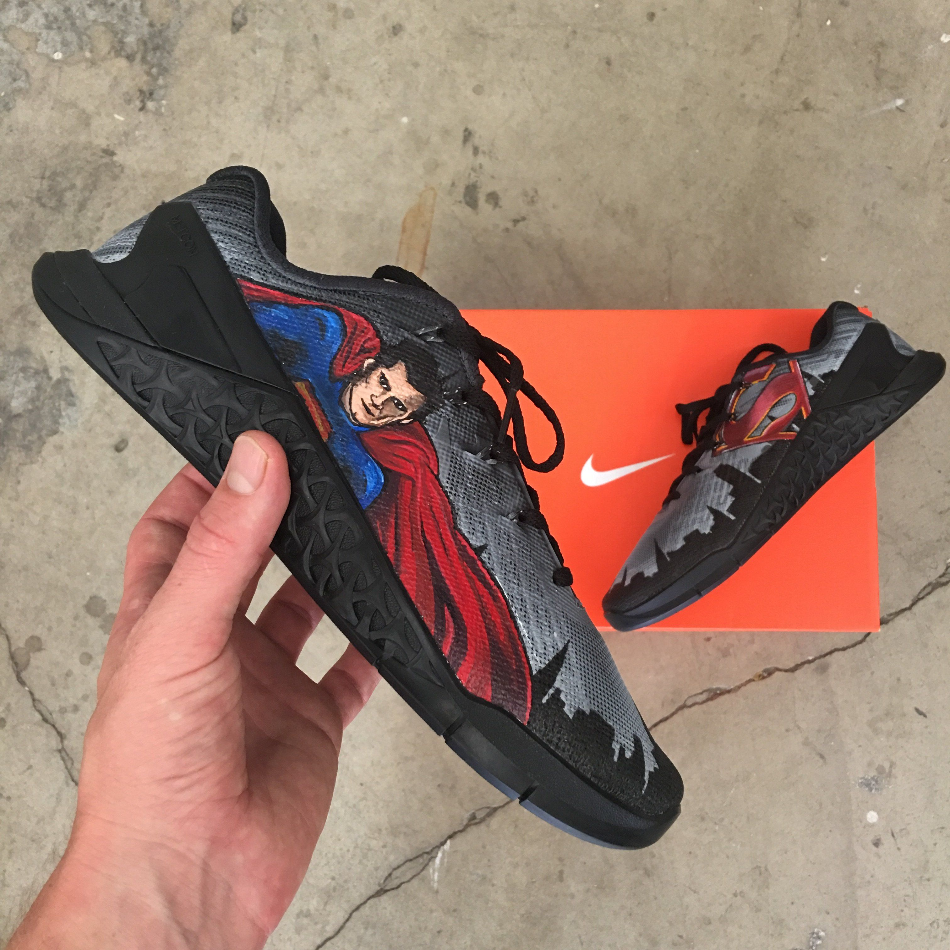 ca9c7b2860e12 Illustrated on these custom Nike Metcon 4 s are Superman Man of Steel on one  side and his shield-like emblem on the other