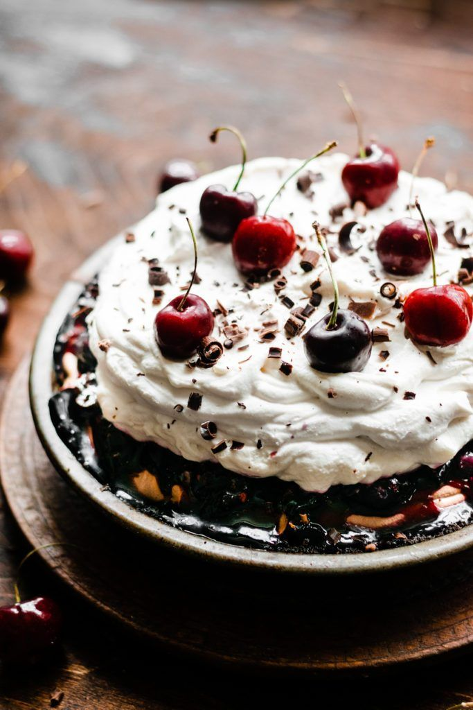 This No Bake Black Forest Pie is made with a chocolate crust, a thick layer of rich chocolate mousse filling, a layer of boozy cherry sauce, and it's all topped off with a mile-high pile of fresh whipped cream! This is a spectacular dessert - you'll sure to fall in love with it!#blackforest #pierecipes #nobakedessert #nobake #nobakerecipes #dessertrecipes #chocolaterecipes #holidaydesserts #blackforestpie #cherry #cherrysauce #boozydesserts #bluebowlrecipes | bluebowlrecipes.com