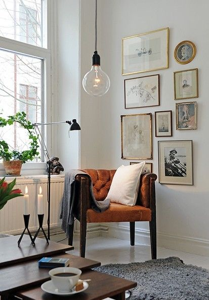 So charming. Vintage. Rust-colored chair. Frame wall. Hanging light fixture.