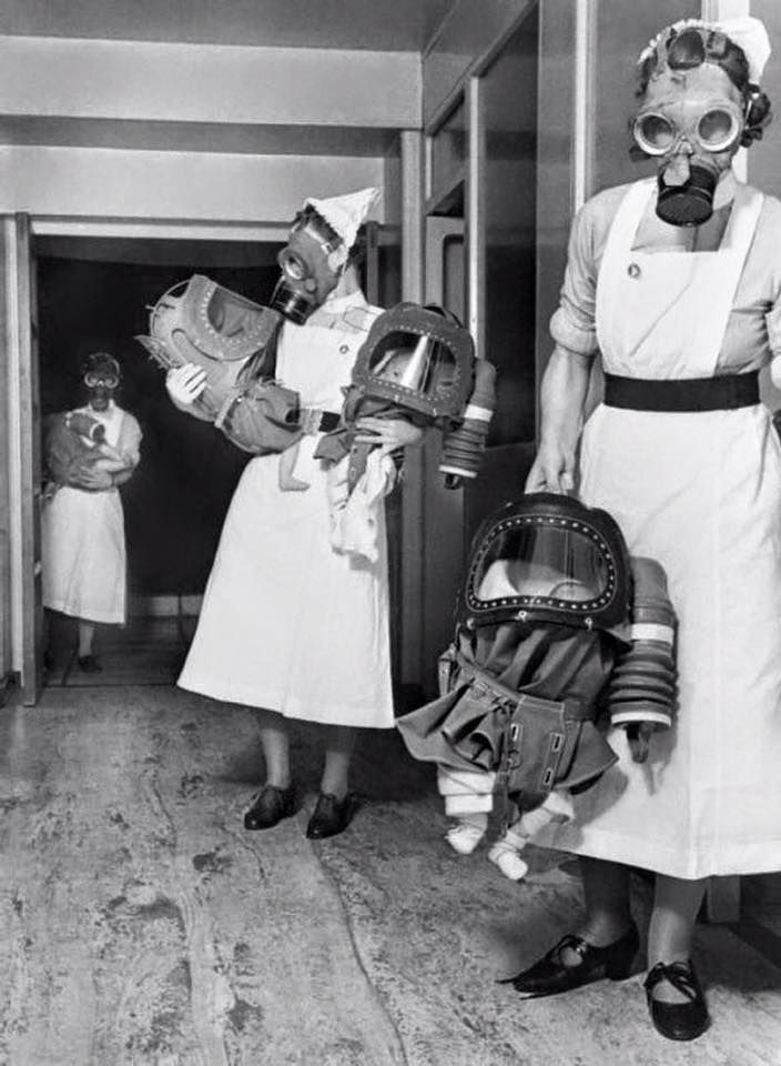 World War II in Pictures — greasegunburgers:Three Nurses carry infants dressed in their specially made Chemical Protective Gear during a drill in London 1940. Three Nurses carry infants...