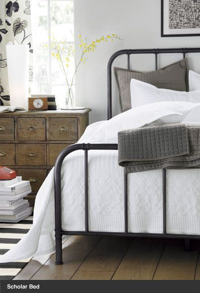 Iron bed, wood floor, neutral accessories and white bed