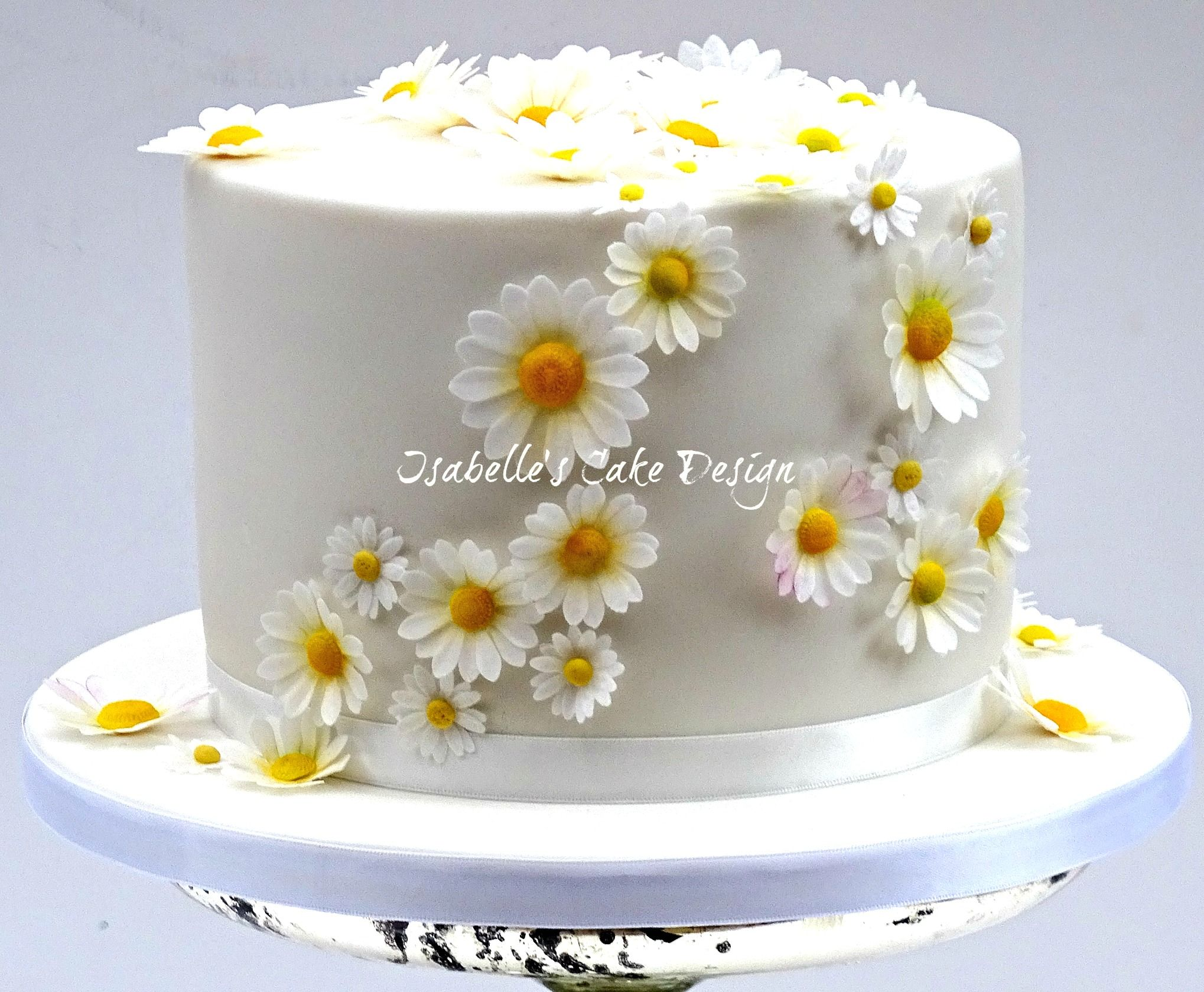 a single tier wedding cake decorated with wafer paper edible daisies