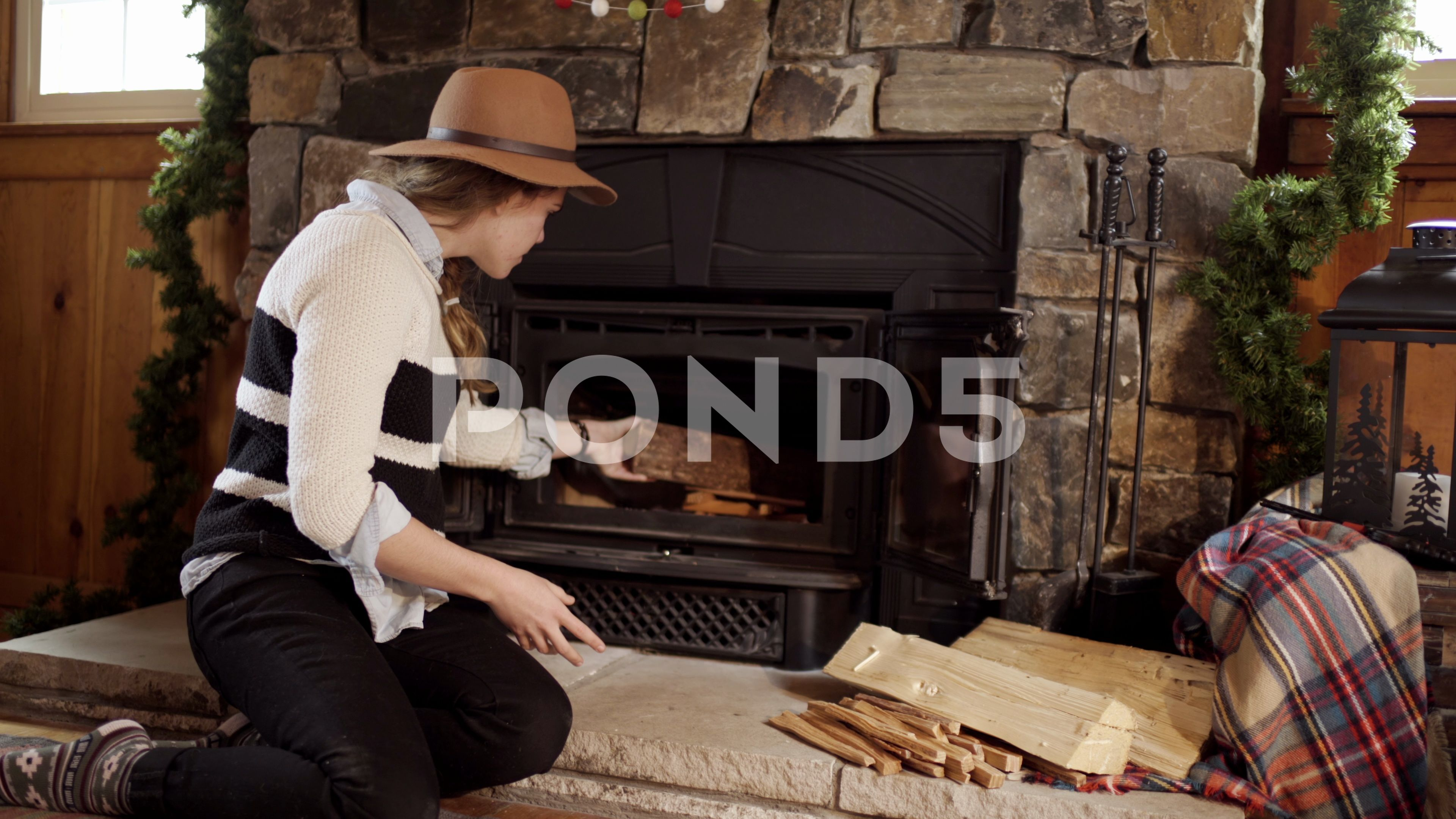 Woman Adds Kindling And Logs To Start A Fire In Fireplace Stock