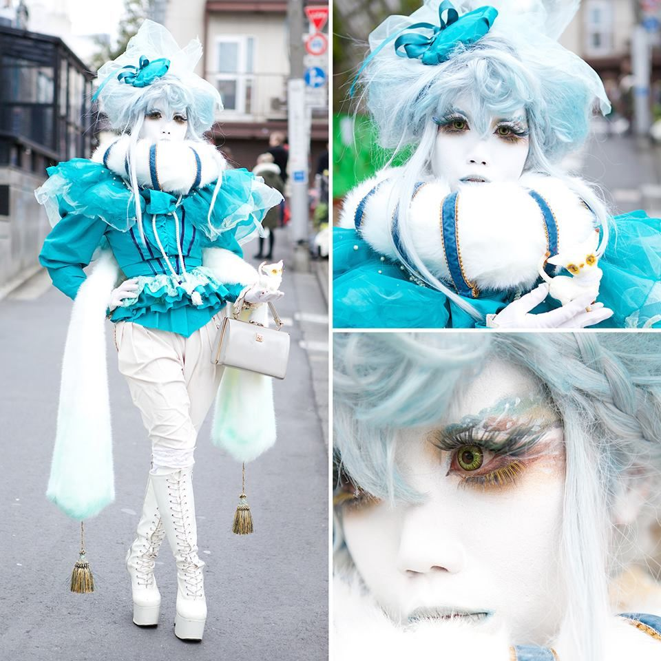 Japanese shironuri artist Minori in blue & white on the street in Harajuku. Minori's look - which is all handmade and vintage - include a faux fur collar and attached scarf with tassels, beautiful eye makeup, a blue top and hat, lace up platform boots, and a small handmade cat.