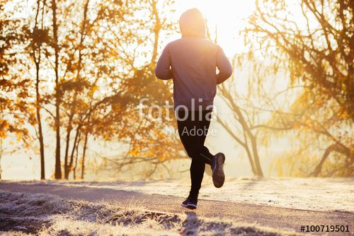 Young man running during autumn, winter morning