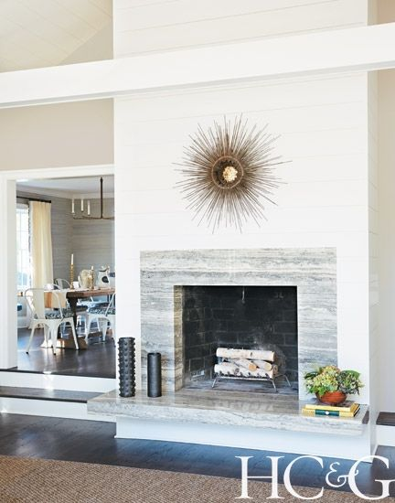 a vintage curtis jere sunburst mirror hangs above the silver travertine fireplace surround in the living room