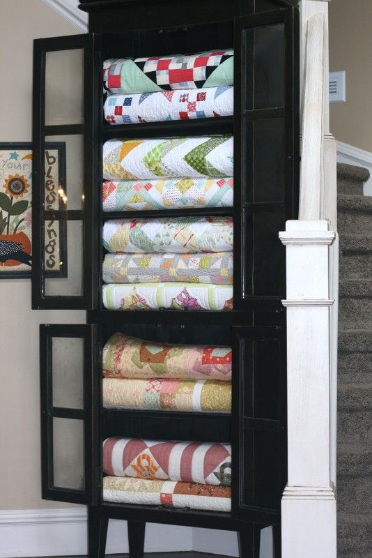 Store quilts in a china cabinet for easy access and nice looking blanket  storage