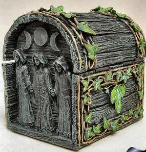This highly detailed box depicts the Maiden, Mother, & Crone on the sides with the Triple Moons carved overhead. The front of the box has a triangle with a pentacle at its center carved just above the black metal hasp; which is perfect for a symbolic twist of wire to lock as part of a wishing or petition spell. The entire box is carved to seem made of wood and is decorated all around with carved and painted vinework. The lid hinges open to reveal the interior space.