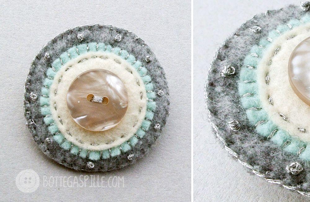 spilla tonda a cerchi concentrici con colori delicati cucita con il filo argento e rifinita nel mezzo con un bottone in madreperla.