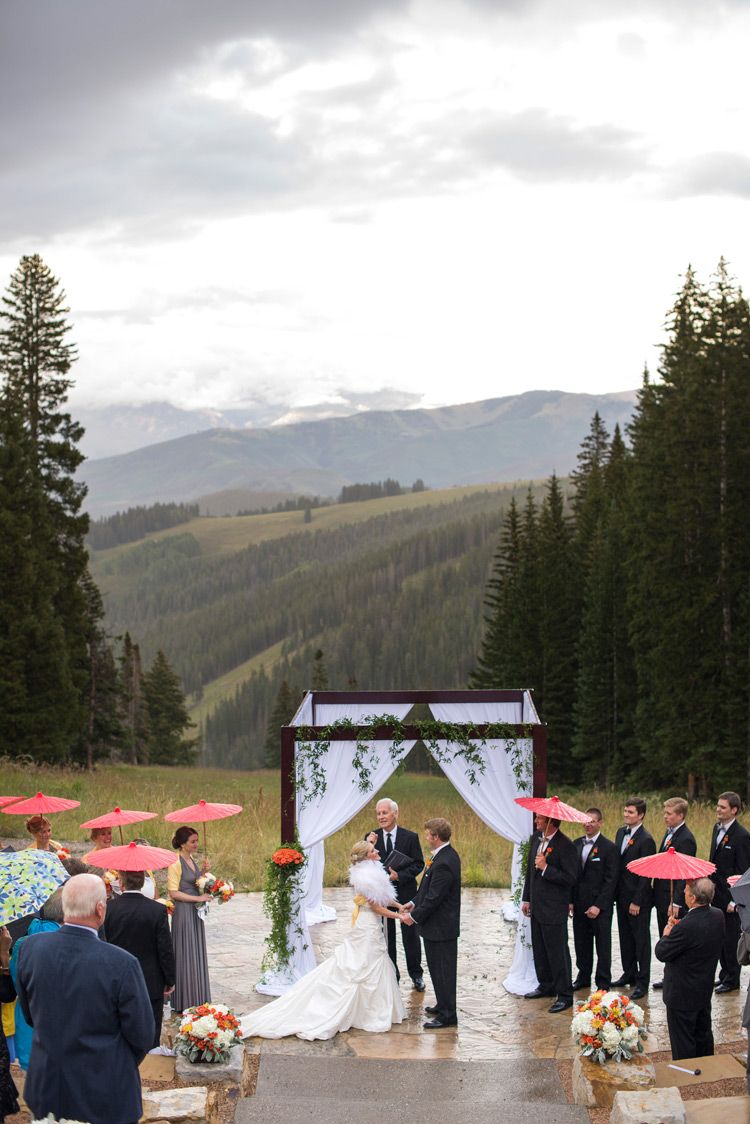 Beaver creek wedding deck, mountain wedding, rainy day, red umbrellas, white fur shawl, ceremony location, bride and groom saying vows