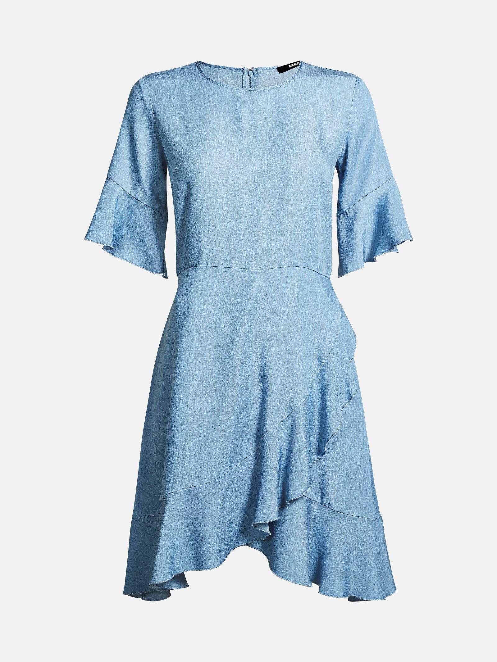 Chambrey denim kjole med volangkanter og knytebelte i ryggen. Kjolen har glidelås i ryggen og den rekker til knærne.  Lys blå