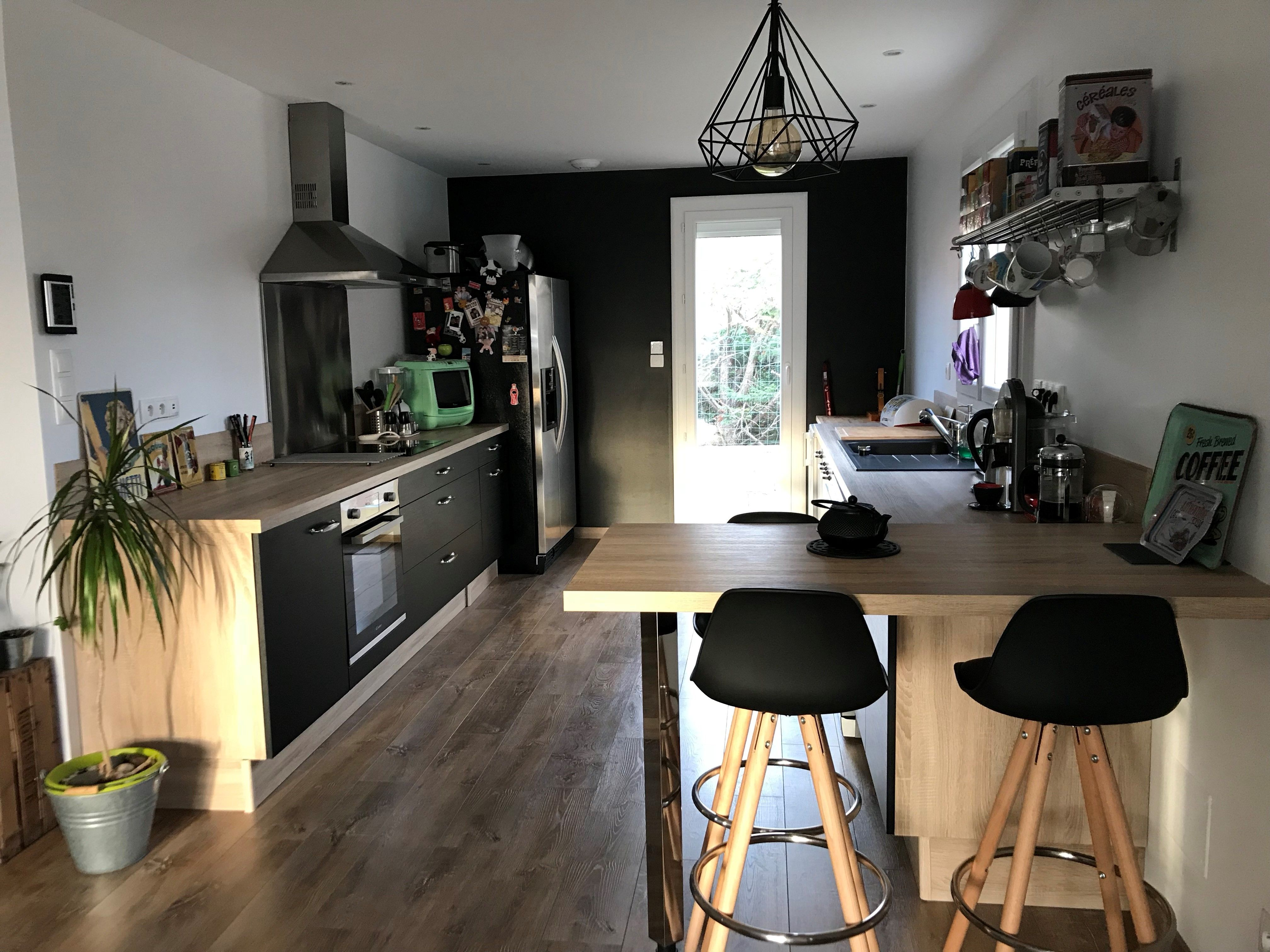 Cuisine ouverte sur le séjour mixant le bois et le noir pour un
