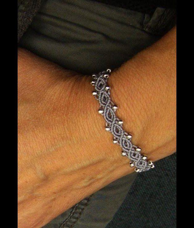 Ein geknüpftes **Armband** in Flieder mit eingearbeiteten silberfarbenen Perlchen.  Es ist größenverstellbar und lässt sich somit individuell anpassen. Material: S-Lon Cord (Nylon)