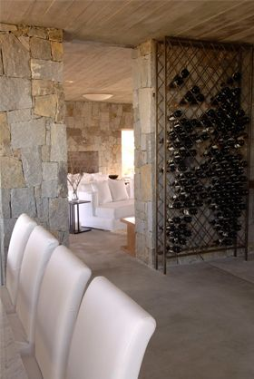 Wine rack against stone wall which matches fireplace stone wall?
