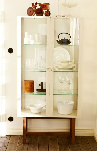 Stockholm Glass Door Cabinet In Beige Filled With Glasses And Plates