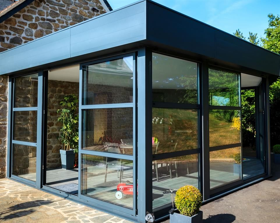 Extension moderne en verre avec un toit plat for Extension villa