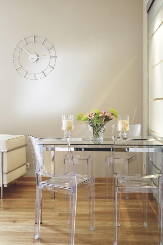 Sillas de policarbonato, junto a una mesa de cristal y acero